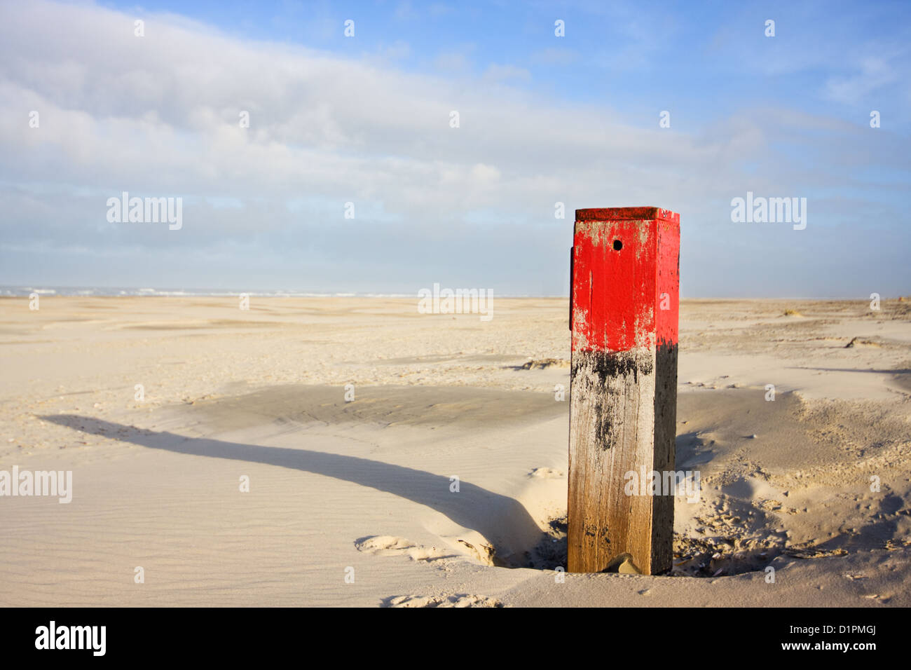 Red beach pole with long shadow on vast beach - Stock Image