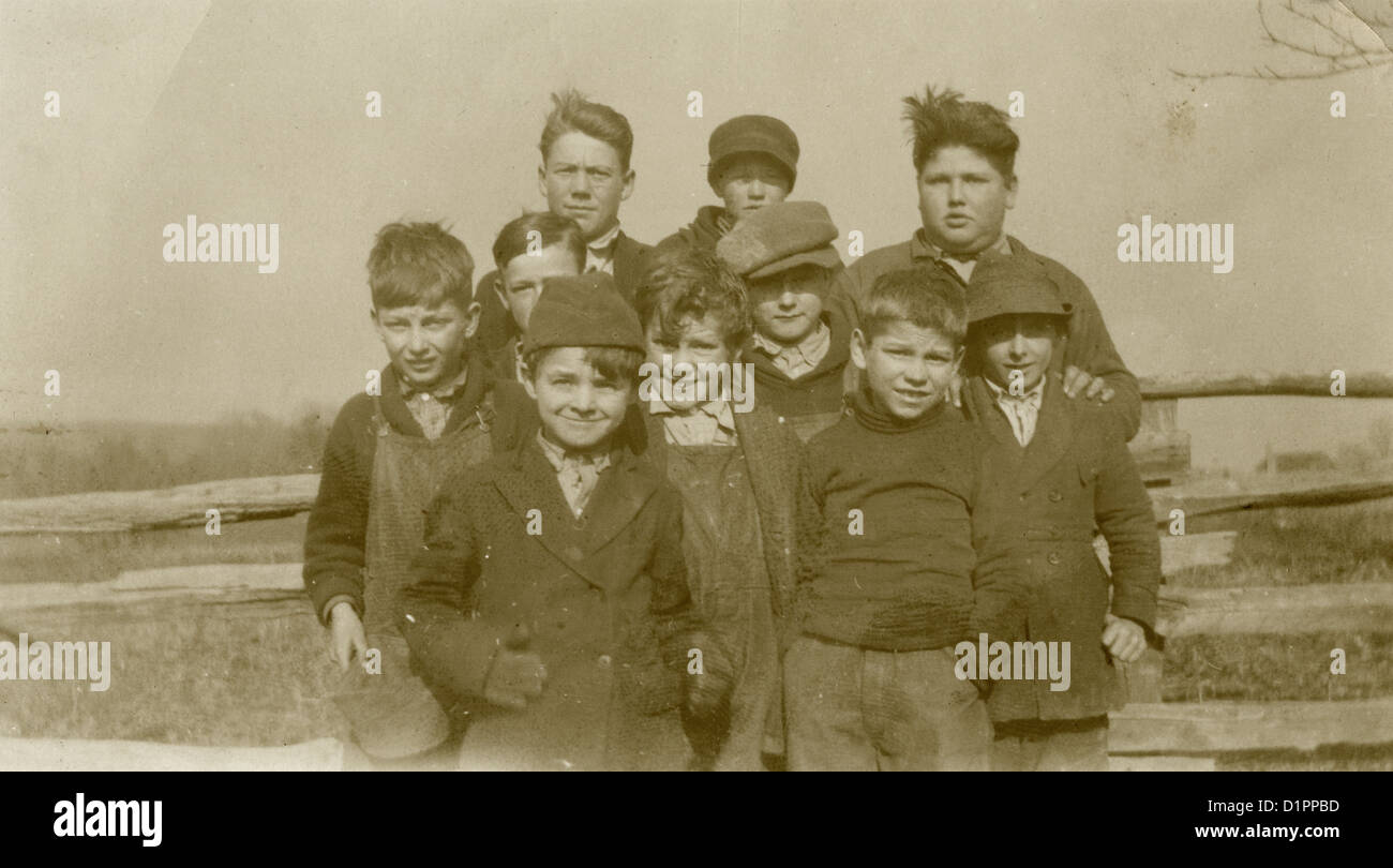 Circa 1910s photograph, group of 10 boys against a wooden fence, probably Massachusetts, USA. - Stock Image