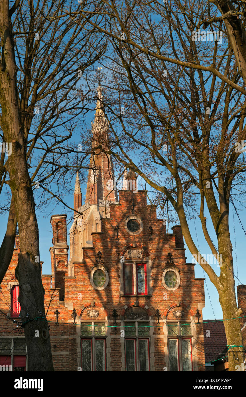 Traditional house gable and Onze Lieve Vrouwekerk Church of Our Lady Bruges Belgium - Stock Image