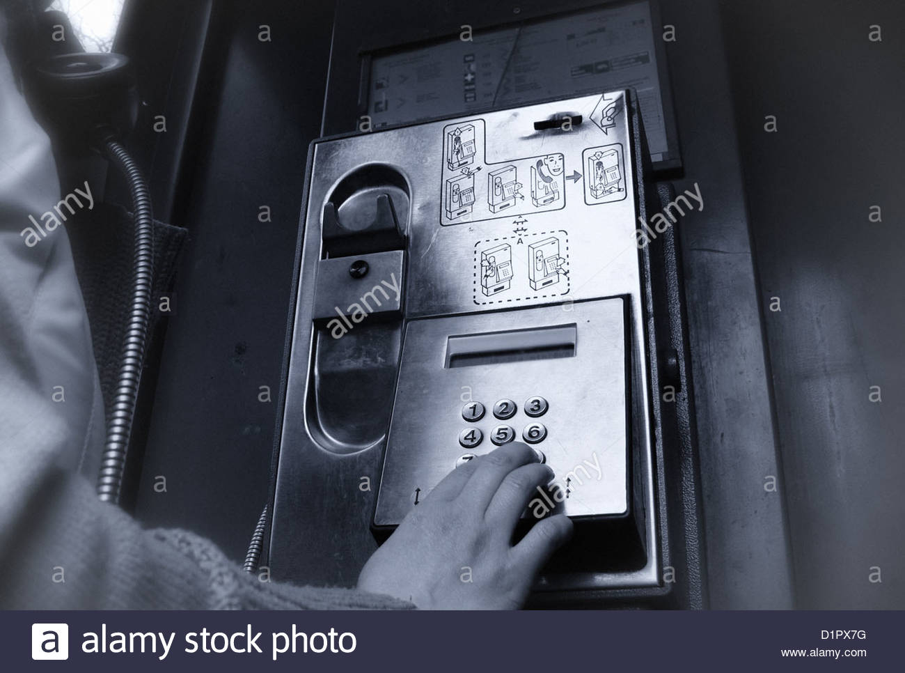 woman dialing in a public phone booth - Stock Image