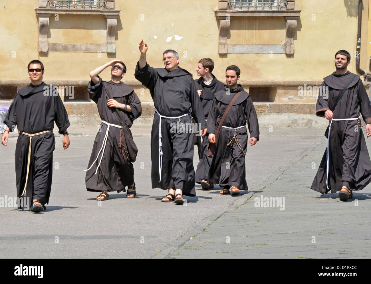 A group of Franciscan Monks dressed in robes sightseeing in Lucca, Italy - Stock Image