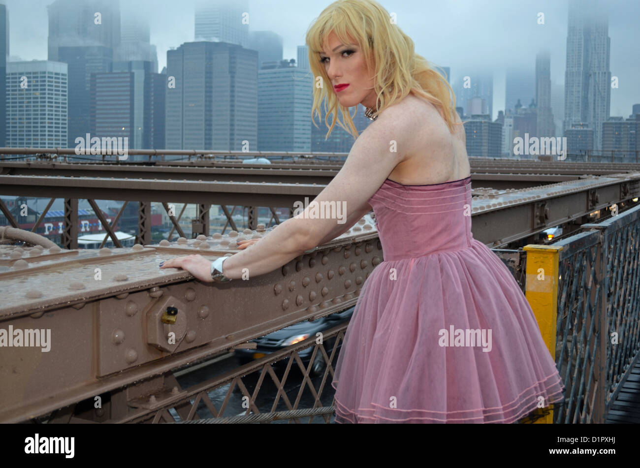 A man in a dress photographed in the rain on the Brooklyn Bridge in New York City - Stock Image