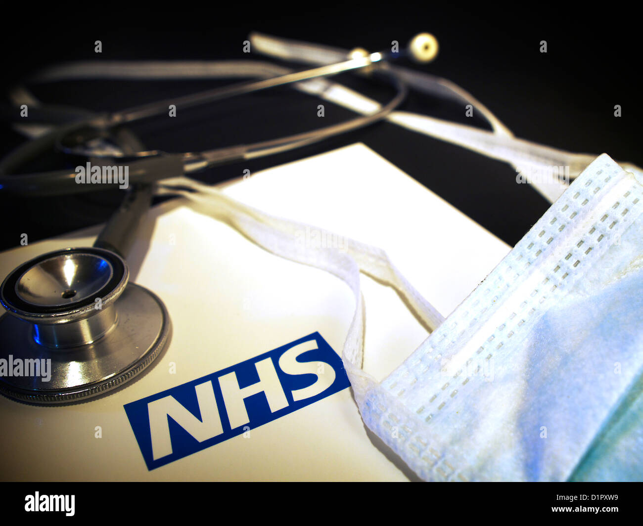 Still life of surgical mask and stethoscope with NHS logo - Stock Image