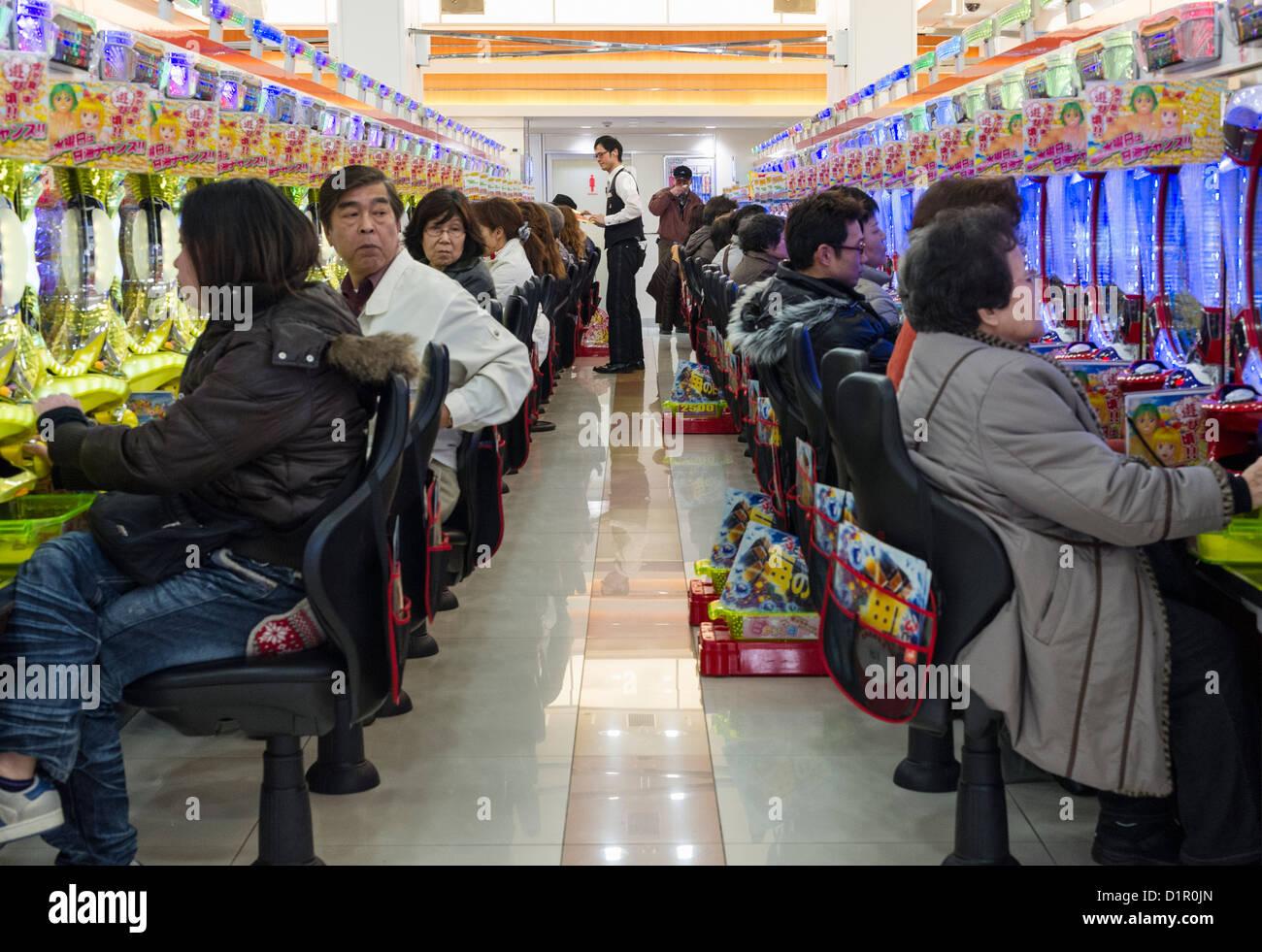 Japanese playing arcade games in Shinjuku, Tokyo - Stock Image