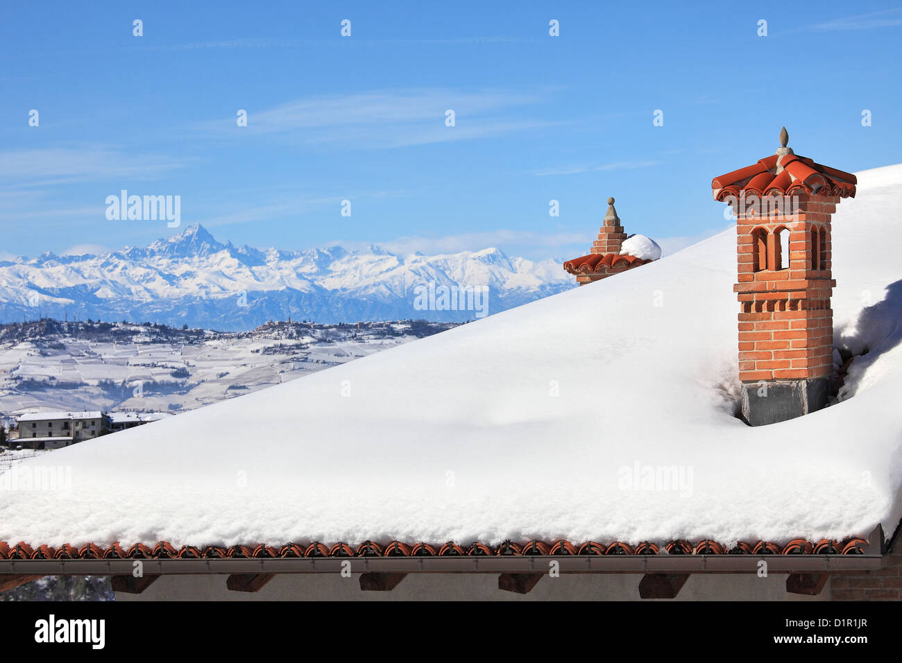 Red brick chimney on the roof covered by snow and snowy mountains on the background under blue winter sky in Piedmont, - Stock Image