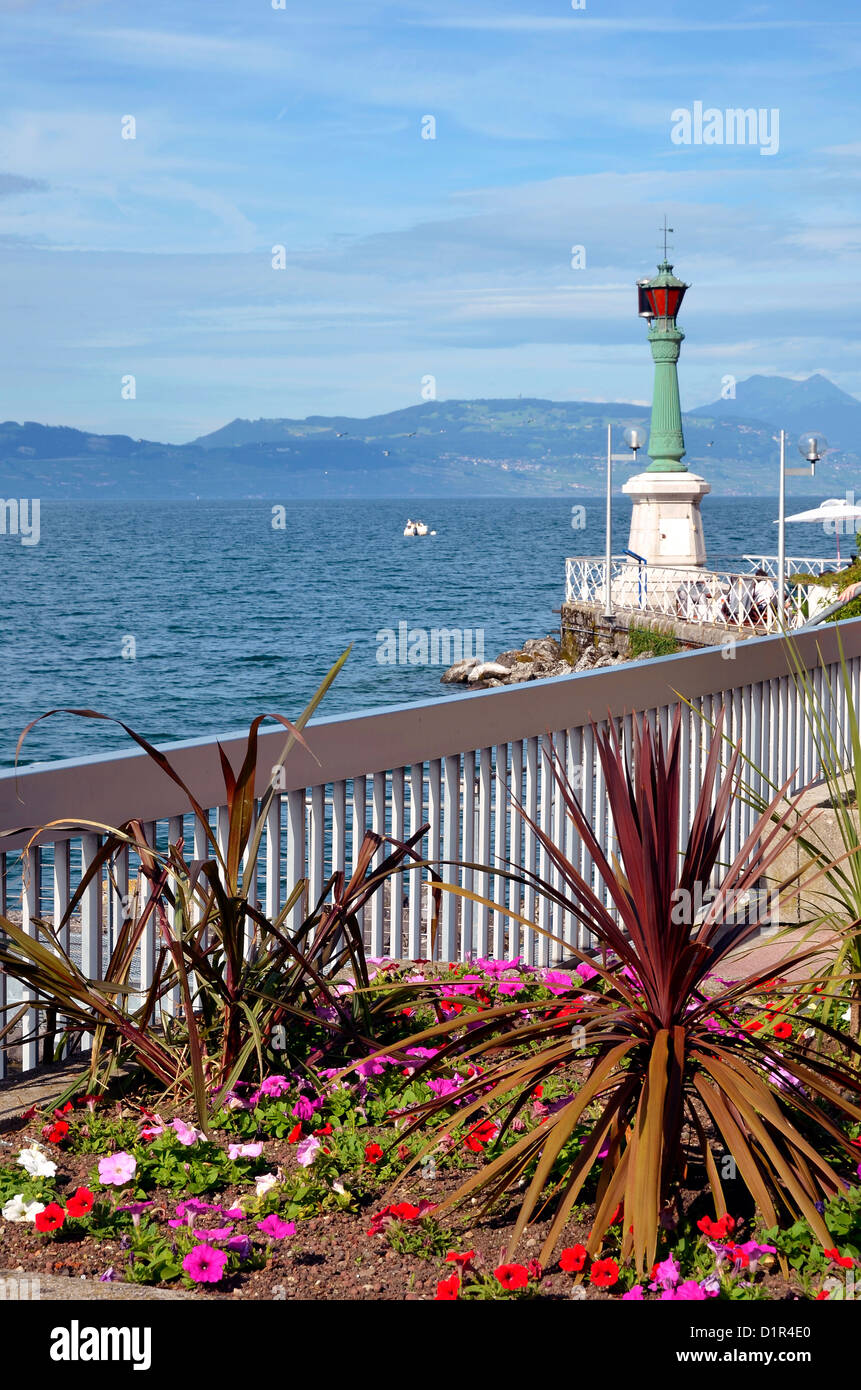Little garden and lighthouse at Evian-les-Bains on the banks of Léman lake to the east of France, commune in - Stock Image