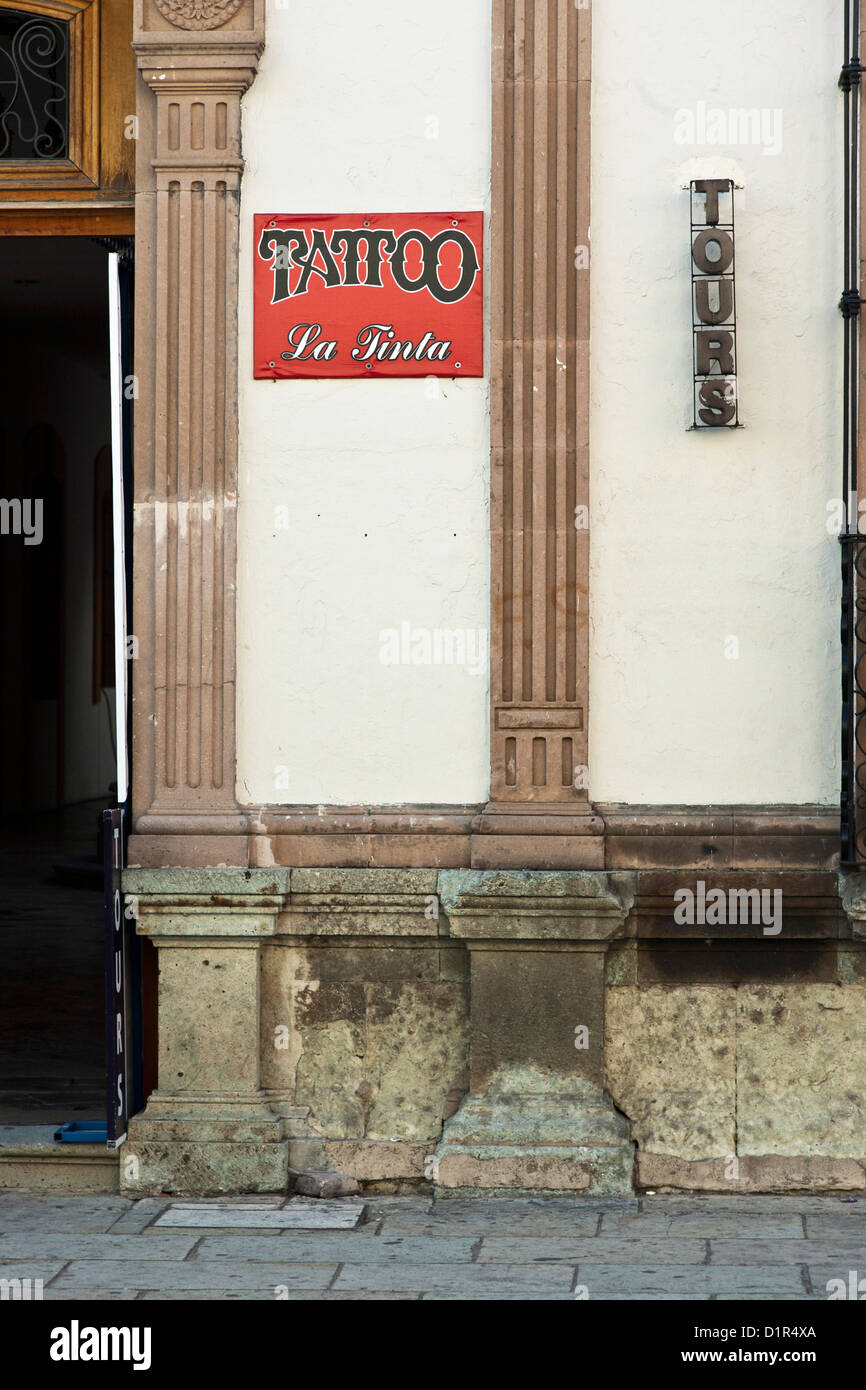 signs advertising tours & a Tattoo parlor on the facade of Spanish Colonial building on Calle Macedonio Alcala - Stock Image