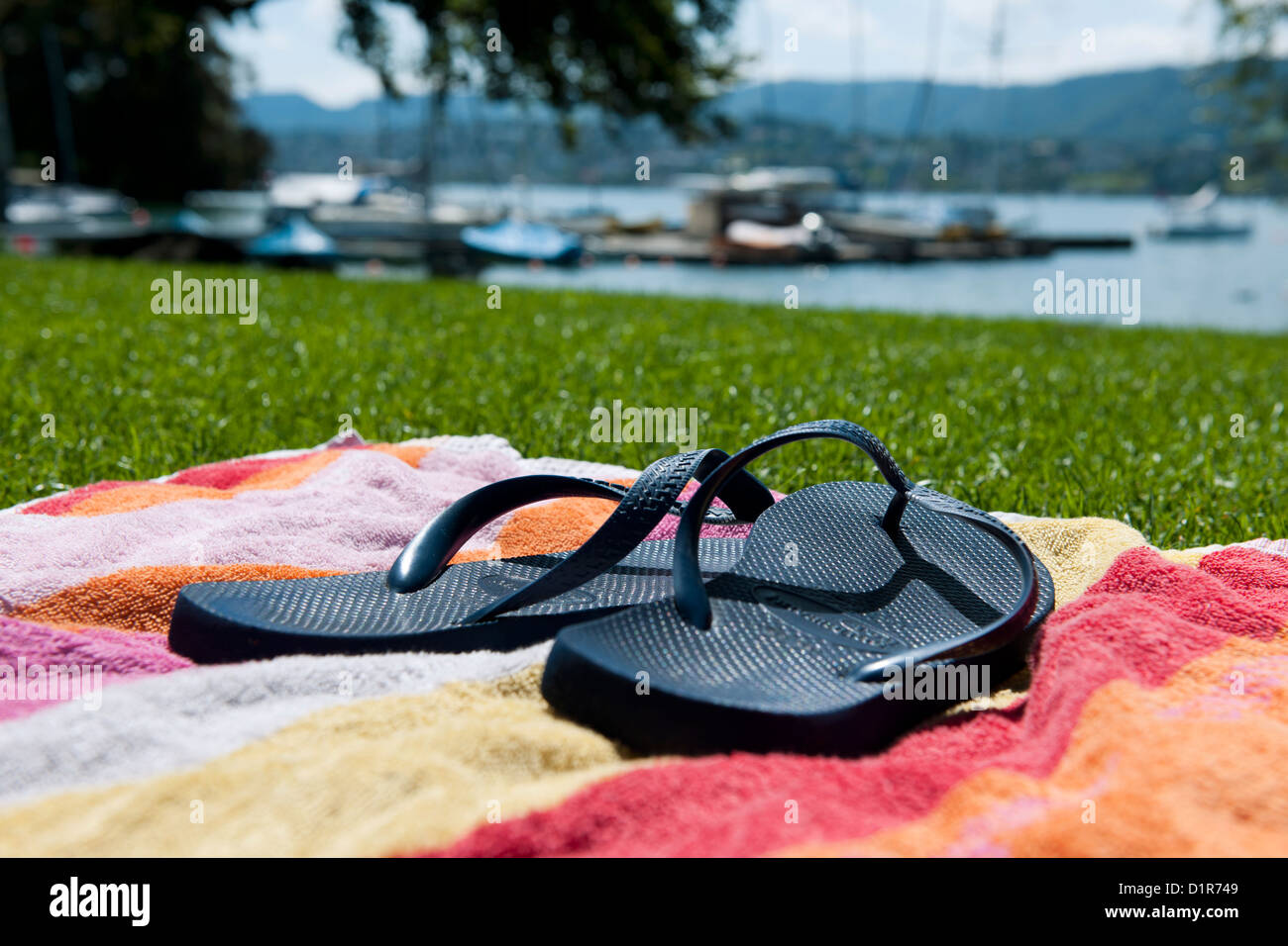 flip flops on a colorful towel with a view to the lake of zurich on a sunny day - Stock Image