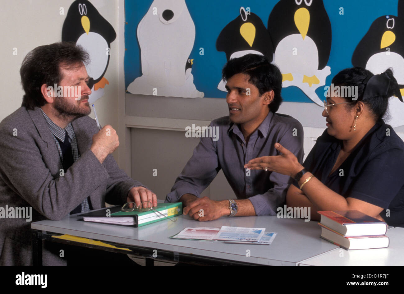 Asian couple in consultation with school teacher - Stock Image