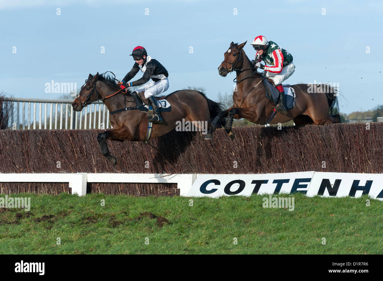 Horses and riders jump a fence at Cottenham Point-to-Point races Cambridgeshire UK - Stock Image