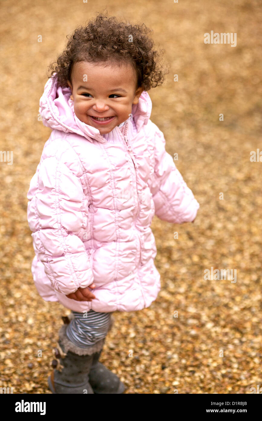 Outdoors portrait of cute happy toddler mixed race girl ...