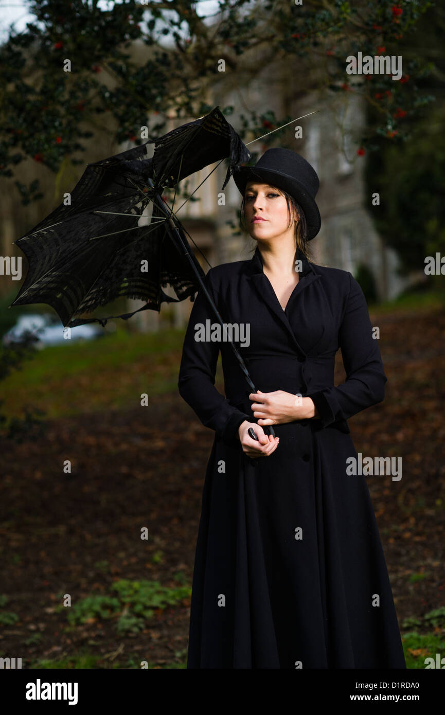 A haughty aristrocratic looking woman, down at heel, holding a tattered umbrella, outside a stately home, UK - Stock Image