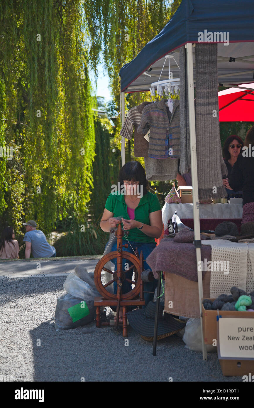 A woman spinning wool at her stall in Riccarton outdoor craft Market, Christchurch, Canterbury, South Island, New - Stock Image