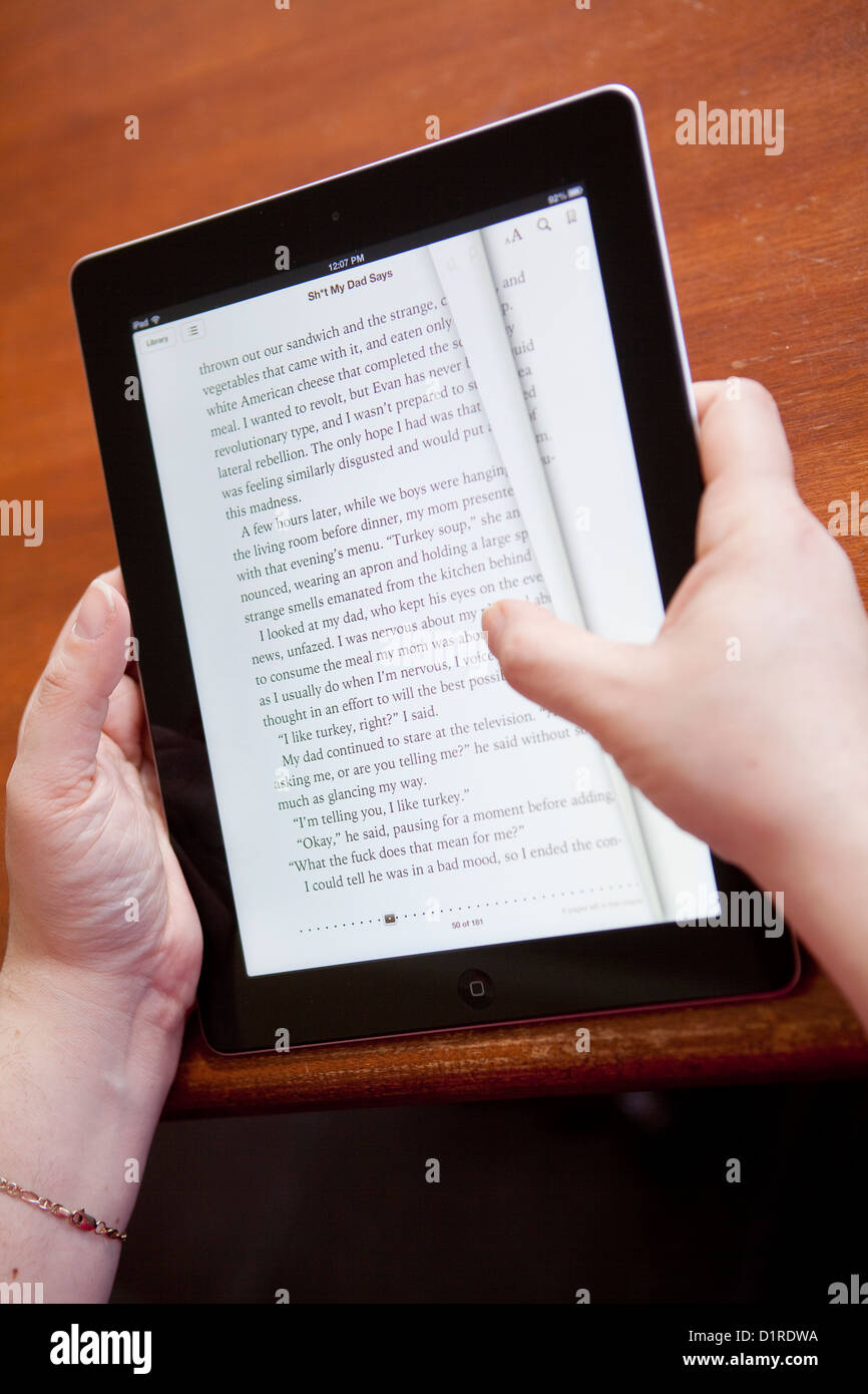 A woman turns the page of an ebook on the iPad 4 iBooks app - Stock Image