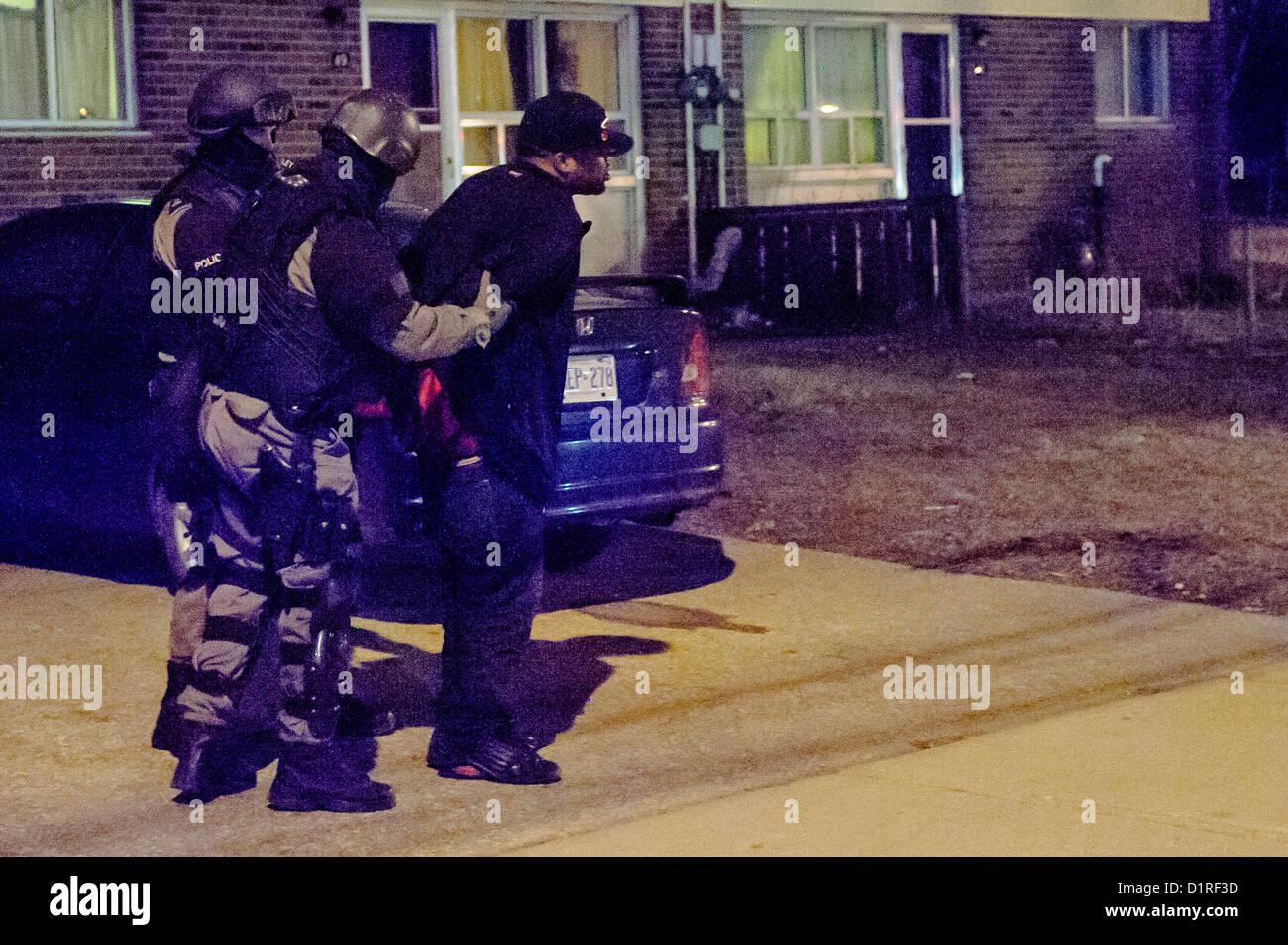 Heavily armed members of Toronto Police execute a search warrant arresting more than a dozen people - Stock Image