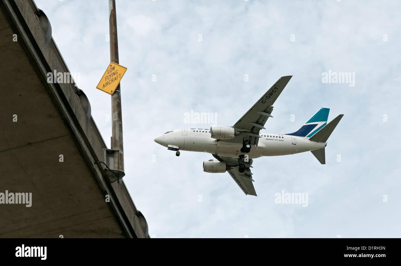 A Westjet  Boeing 737 airliner flying low over the Arthur Laing Bridge just before landing at Vancouver International - Stock Image