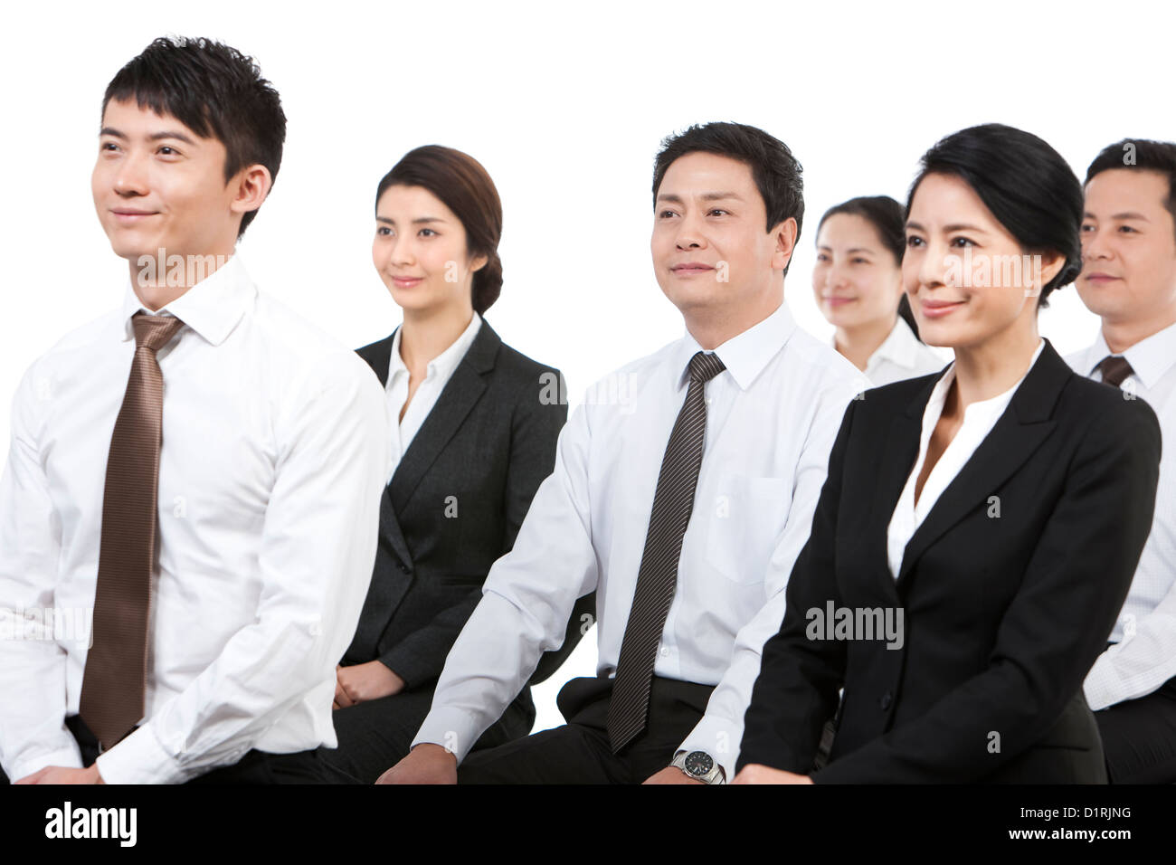Cheerful business persons sitting together in a meeting - Stock Image