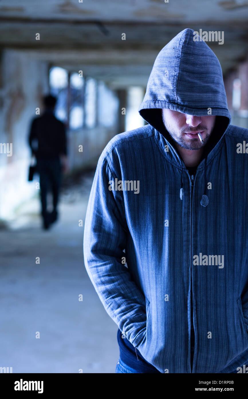 Smoking Criminal with Hood Walking in a Slum Corridor - Stock Image