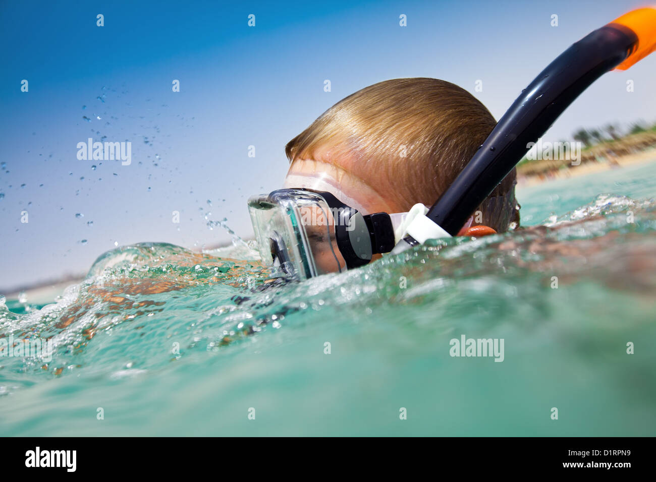 boy floats in the sea - Stock Image