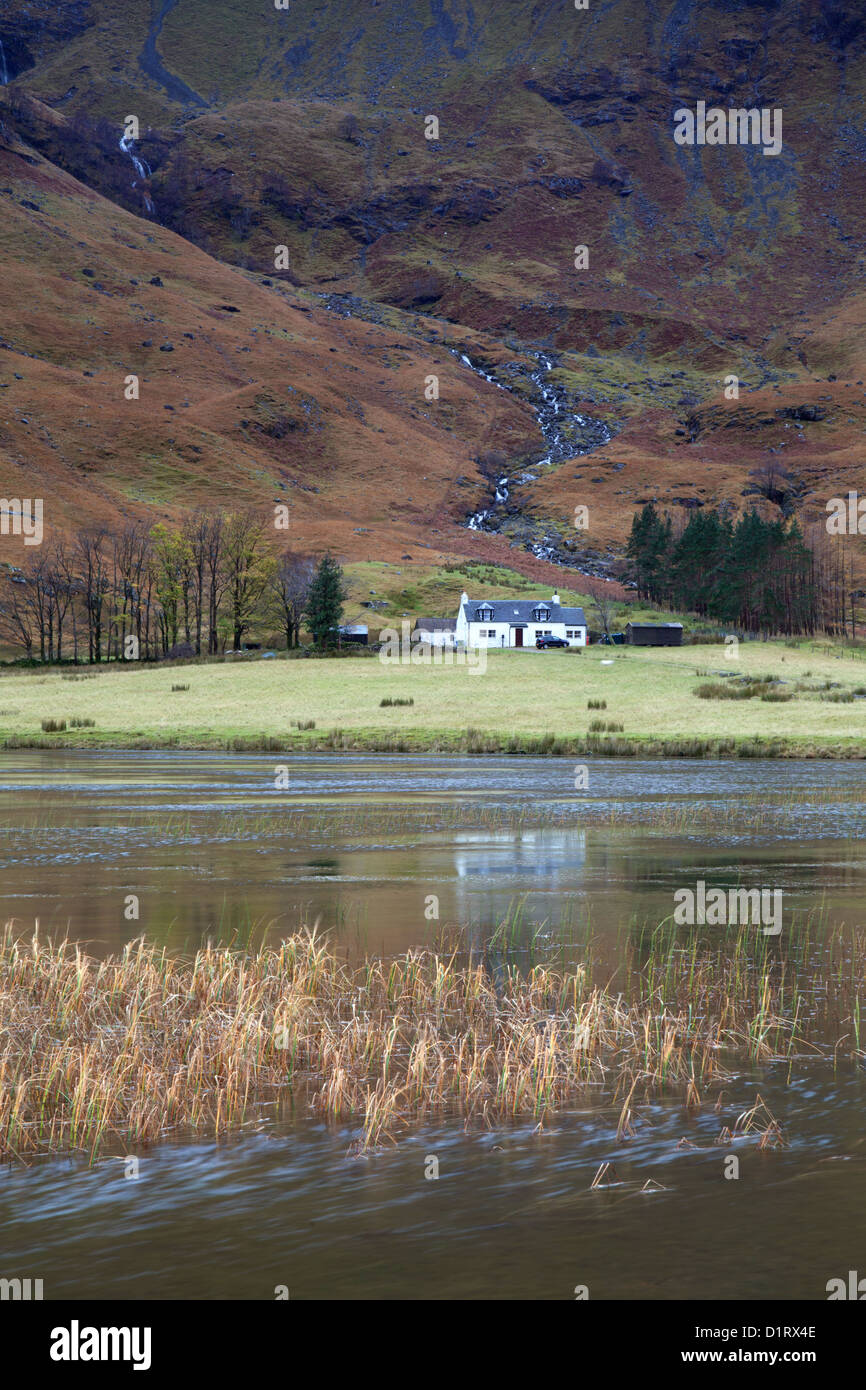 Loch Achtriochtan Glencoe Scotland small white cottage at the base of a fell. - Stock Image
