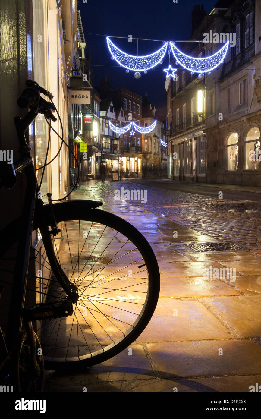 Bicycle on Trinity street Cambridge at night. Christmas lights reflecting on a wet pavement. - Stock Image