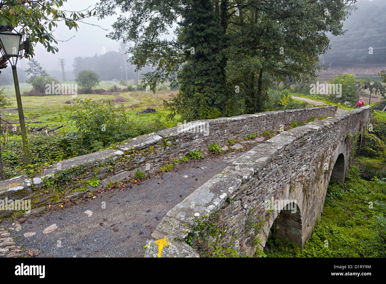 stone pilgrimage bridge Ponte Aspera over Rio Celeiro, Sarria Spain, a painted yellow arrow marks the Camino Way - Stock Image