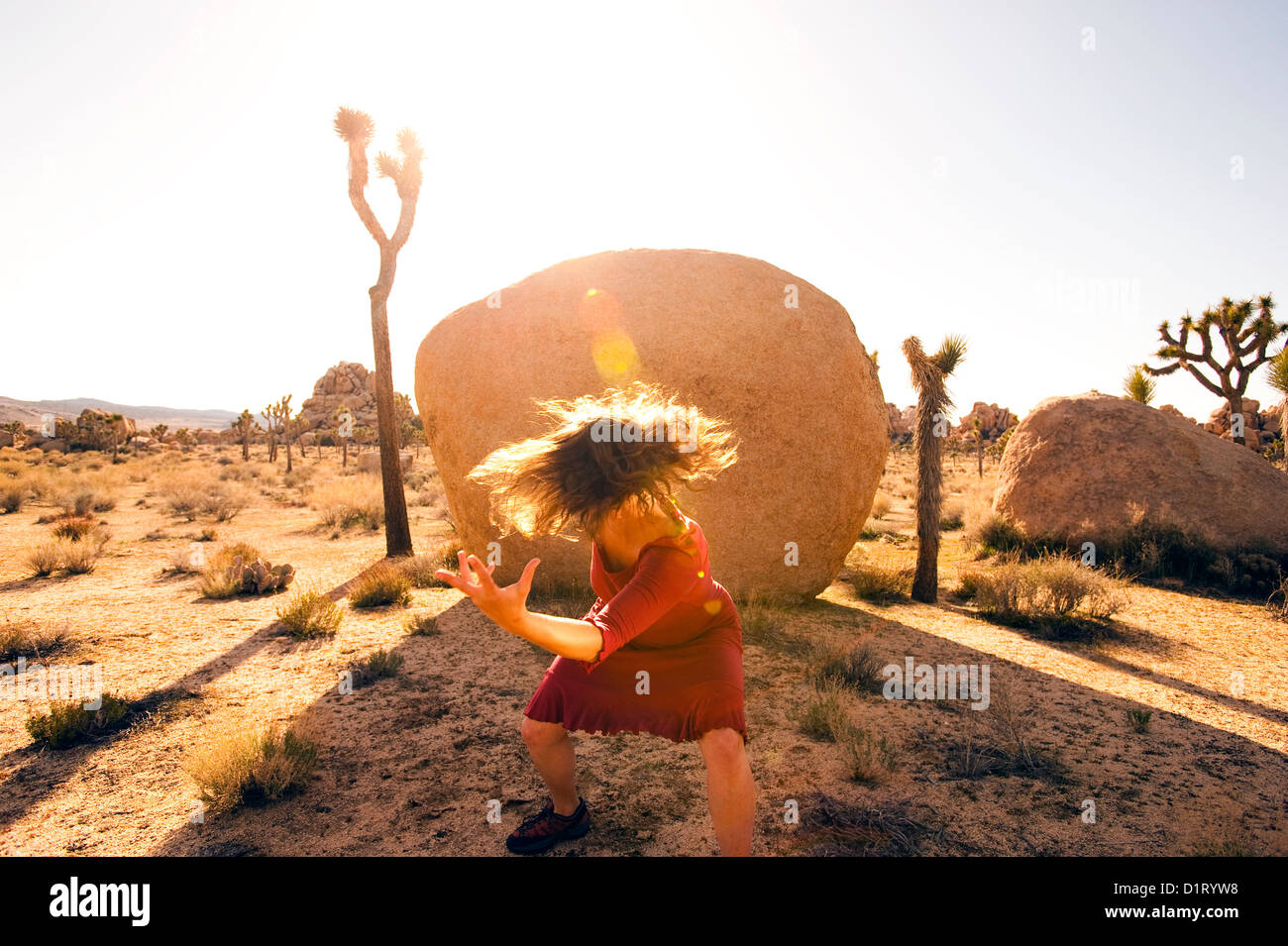 Intense wild woman dancing in the desert. - Stock Image