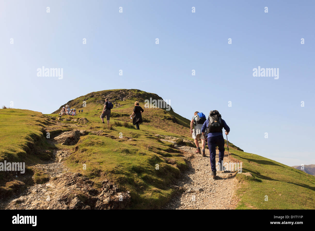 People walking on worn eroded path up Catbells mountain ridge in Lake District National Park on a sunny weekend - Stock Image