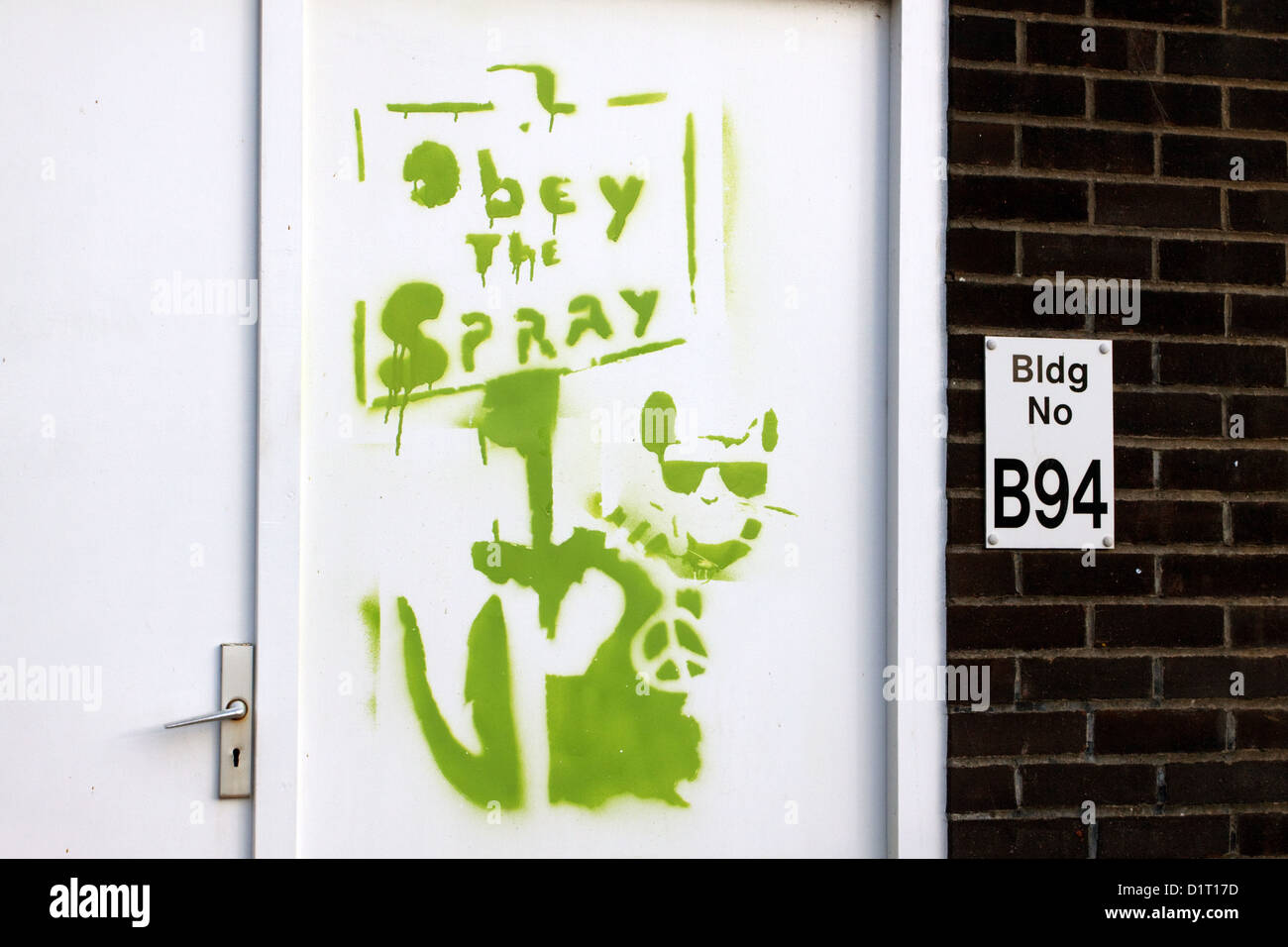 Green stencilled Banksy style placard rat with CND badge and sunglasses holding a sign 'Obey the Spray' - Stock Image