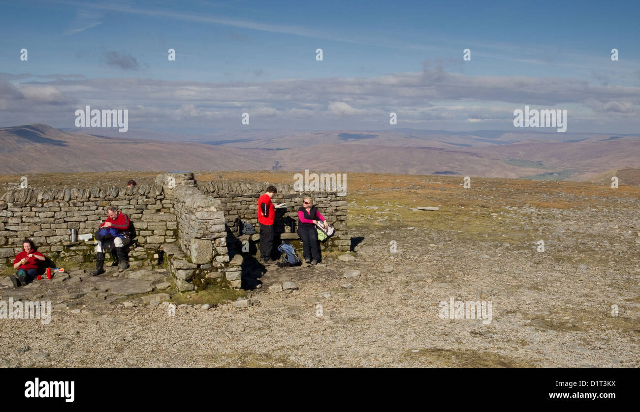 Walkers enjoying a well earned break on the summit of Ingleborough in the Yorkshire Dales - Stock Image