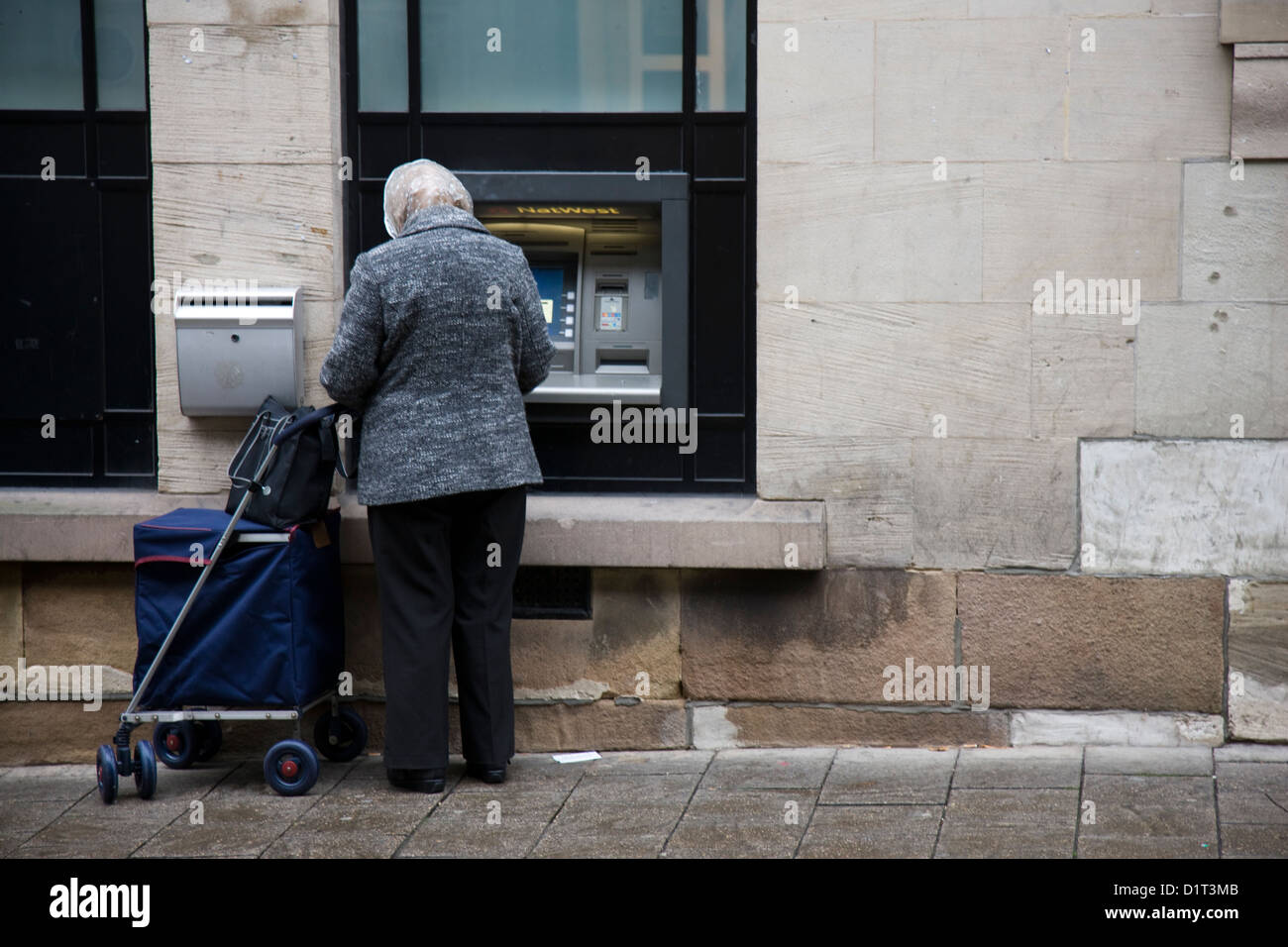 Old lady with shopping trolley using a cashpoint in Chester, UK - Stock Image
