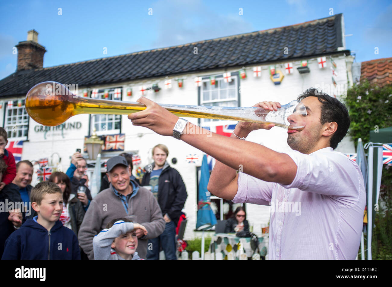 Young Man Drinking Yard of Ale at Village Pub During Queen's Diamond Jubille Celebrations - Stock Image