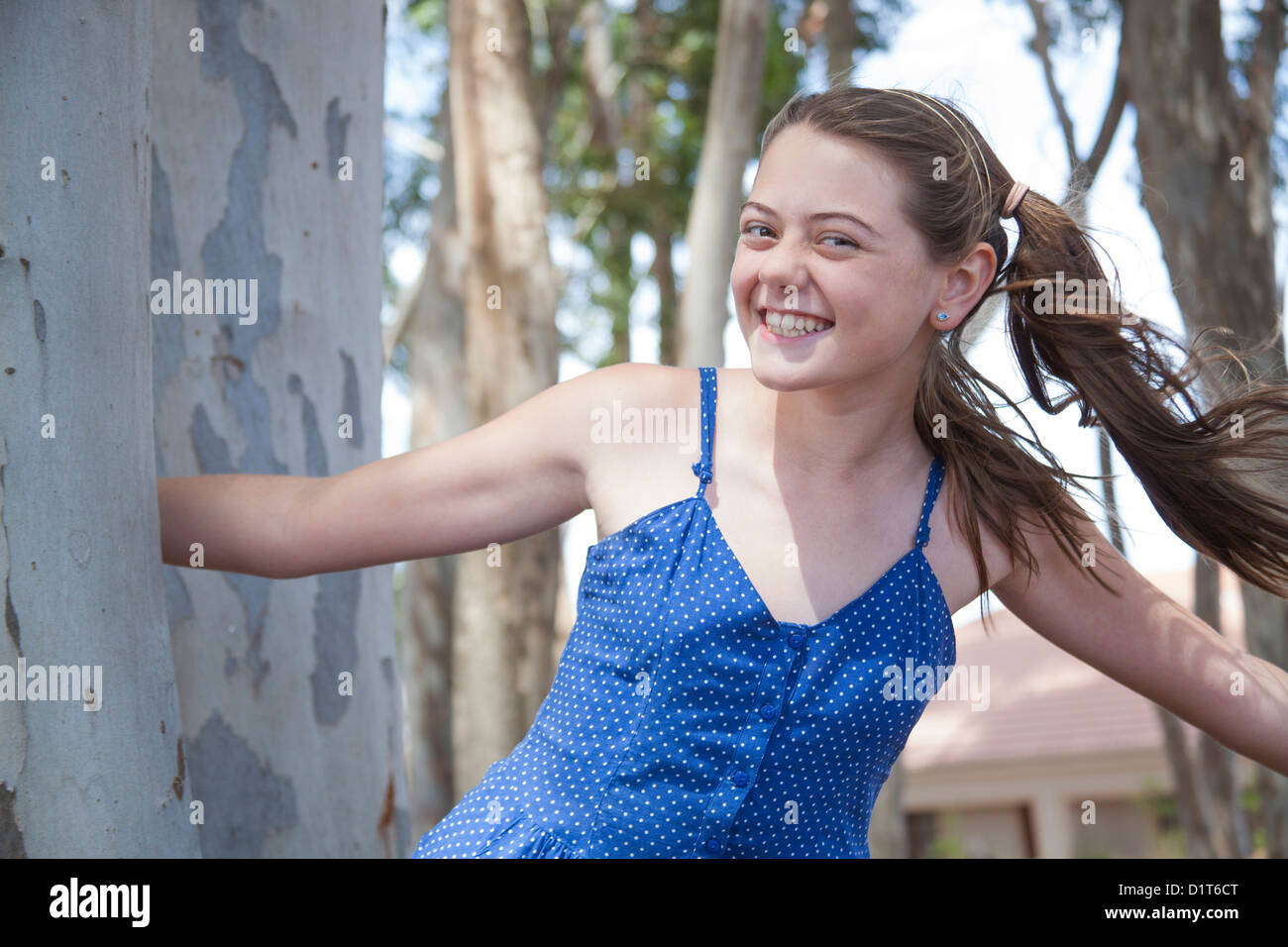 a young girl plays hide and seek in the woods - Stock Image