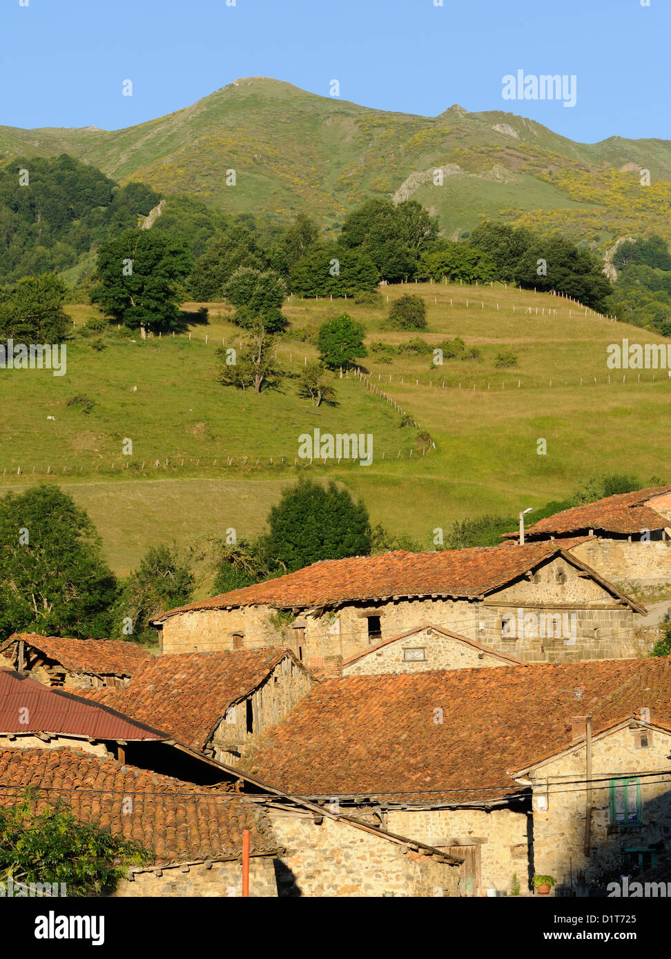 Meadows and mountains above the tiled roofs of the village of Caloca. Caloca, Cantabria, Spain. - Stock Image
