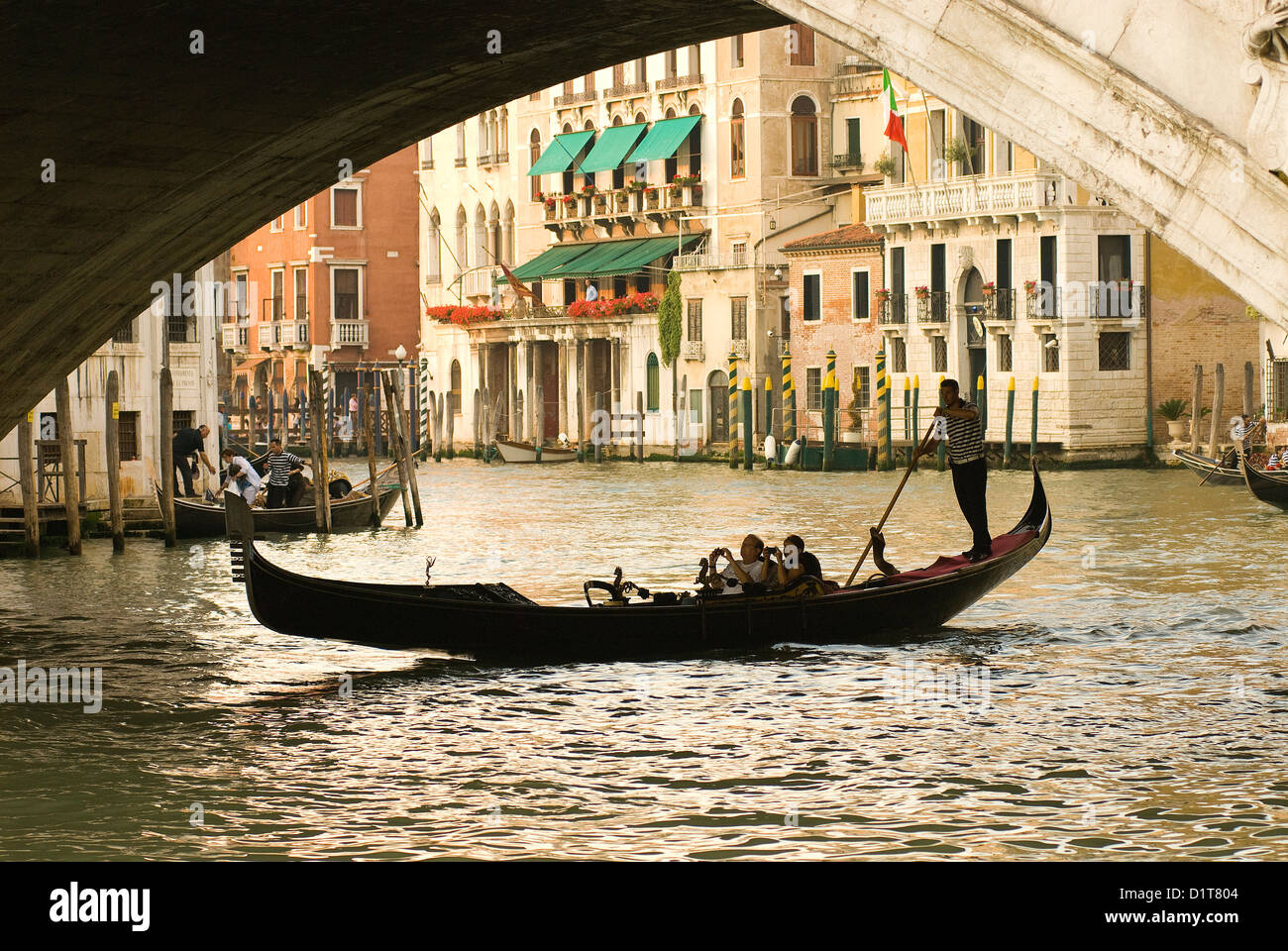 Italy, Venice. Tourist take snap shots from a gondola as they pass under the Rialto Bridge. - Stock Image