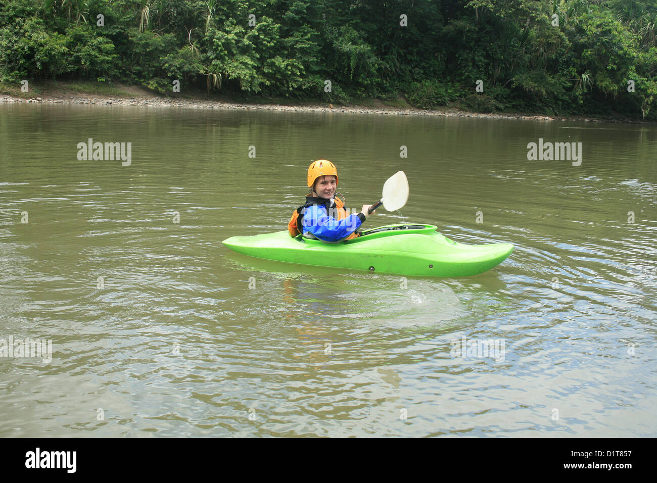 A male teenager paddling a kayak down the Napo River in the Ecuadorian rain forest near Tena, Ecuador - Stock Image