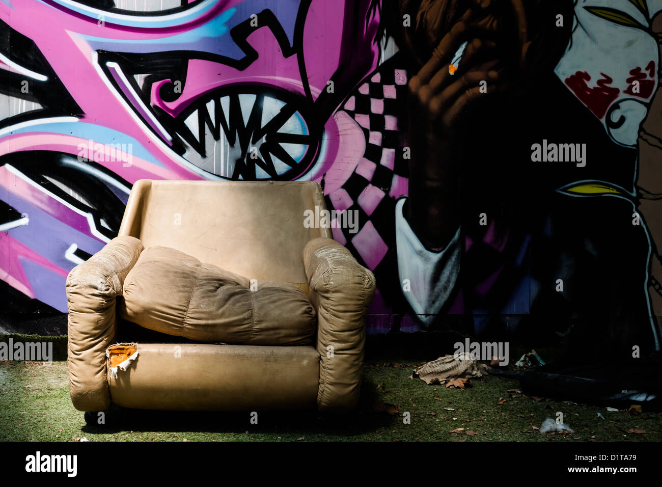 Abandoned armchair with graffiti background - Stock Image