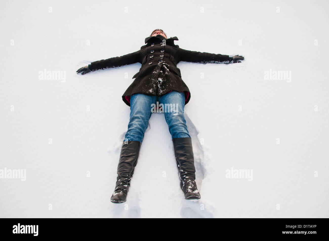 An image of girl lying at groung in winter - Stock Image