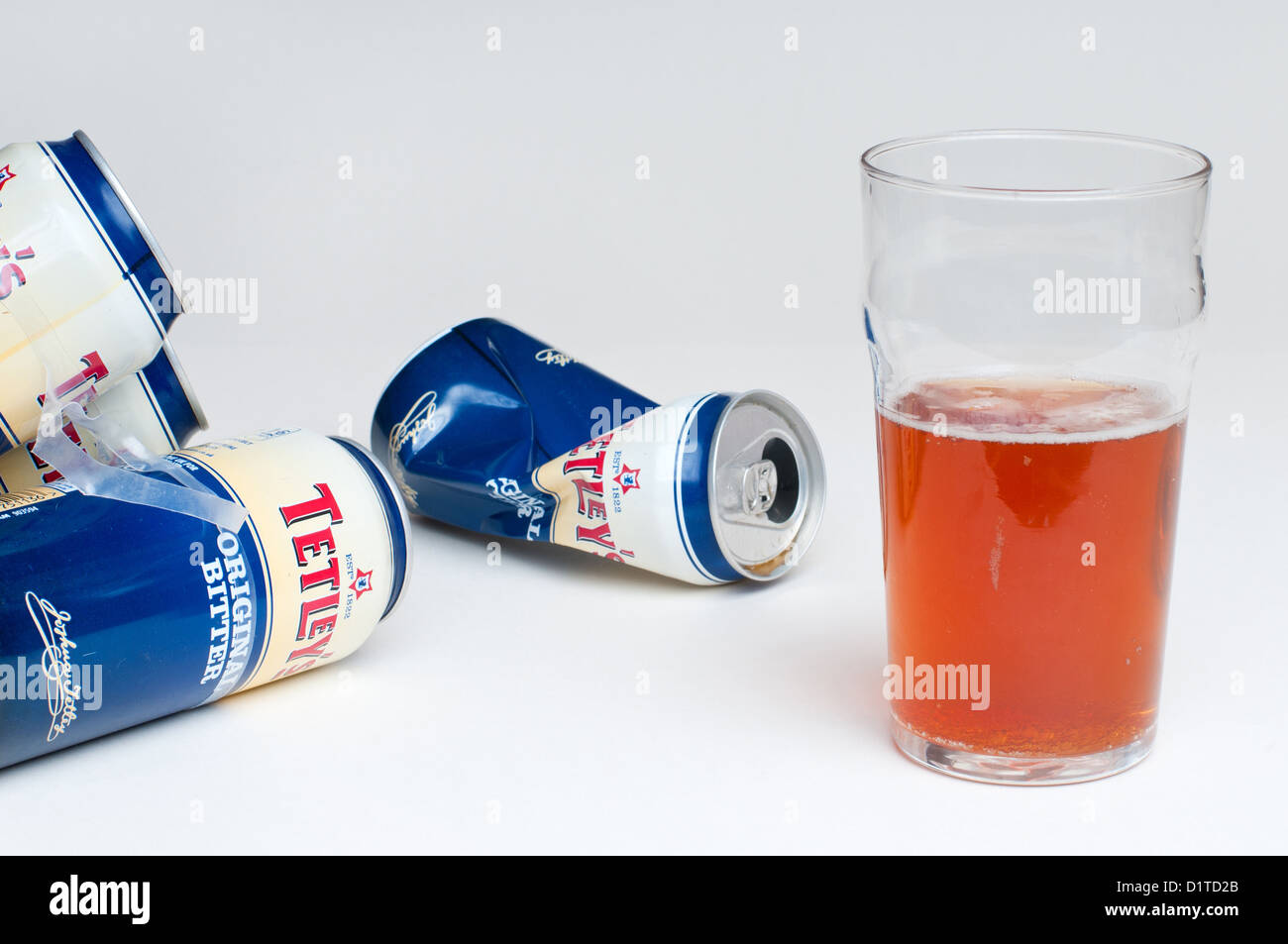 A half empty pint beer glass with full and empty beer cans on a table. - Stock Image