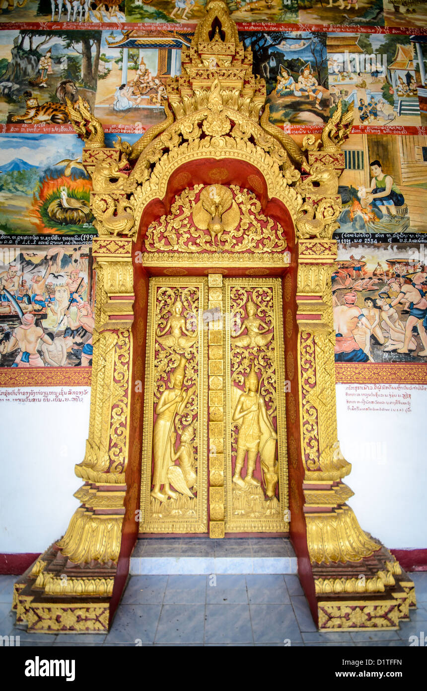 LUANG PRABANG, Laos - A guilded door surrounded by ornate paintings on the exterior of Wat Phonxay Sanasongkham - Stock Image