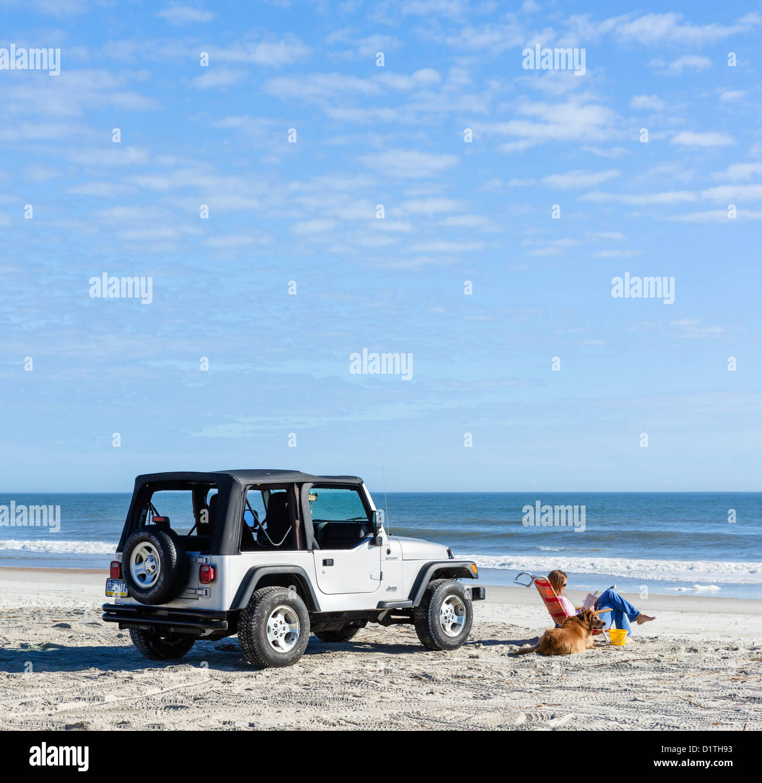 Young woman and her dog sitting by a Jeep Wrangler, Seaside Park Beach, Fernandina Beach, Amelia Island, Florida, - Stock Image