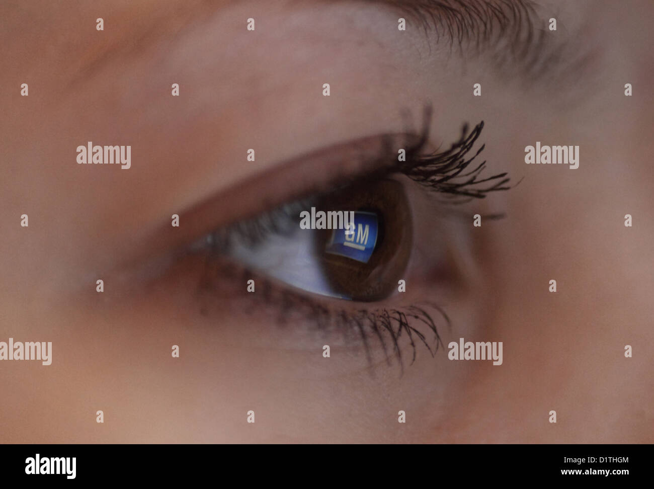Berlin, Germany, mirroring the General Motors logo in the eye of a woman - Stock Image