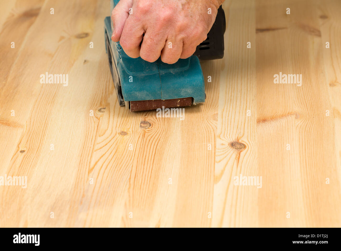 Man Holding A Belt Sander On Pine Floor Or Table Sanding Surface