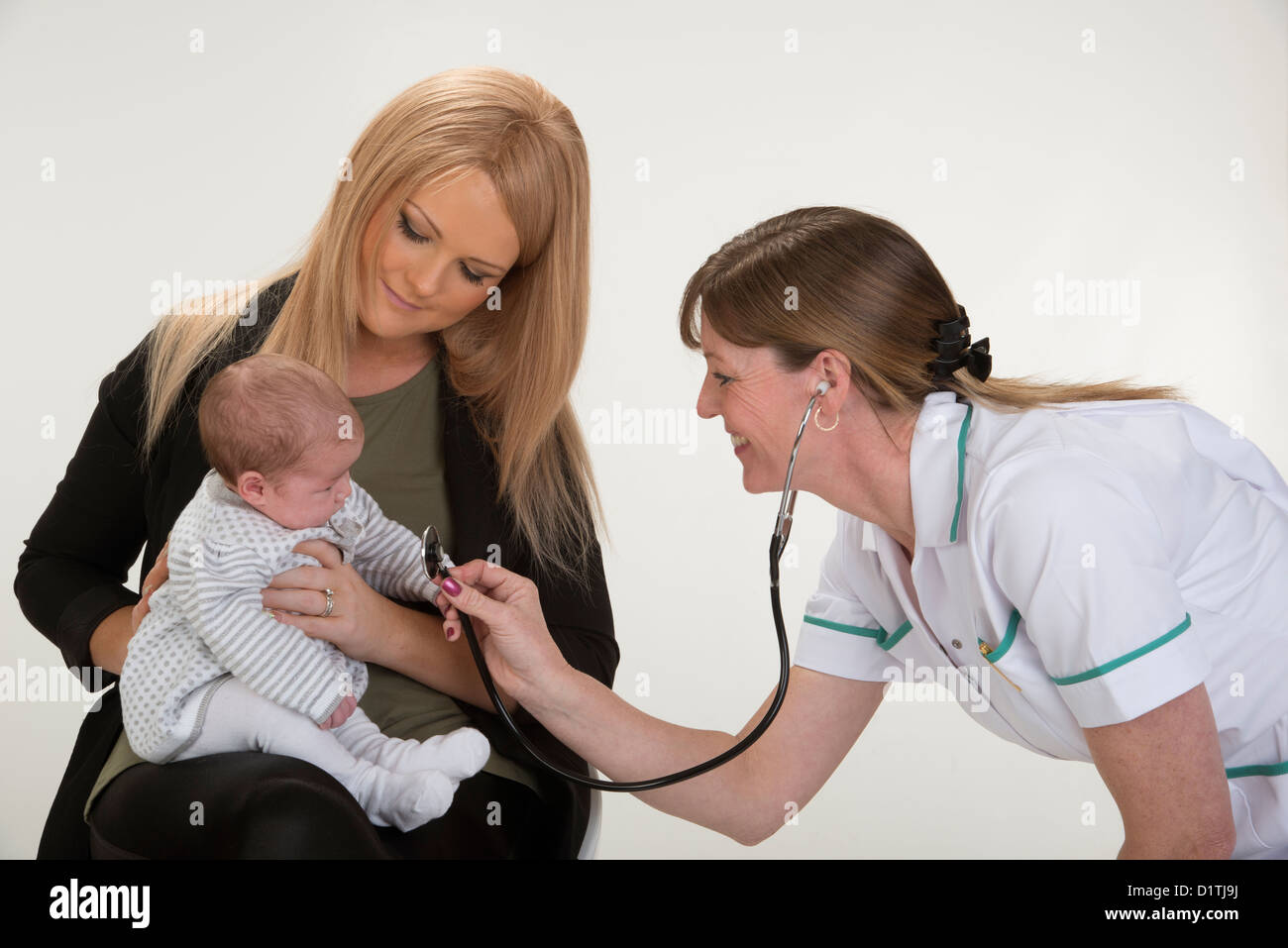 Postnatal checkup for a mother with 4 week old baby girl. Nurse holding stethoscope - Stock Image