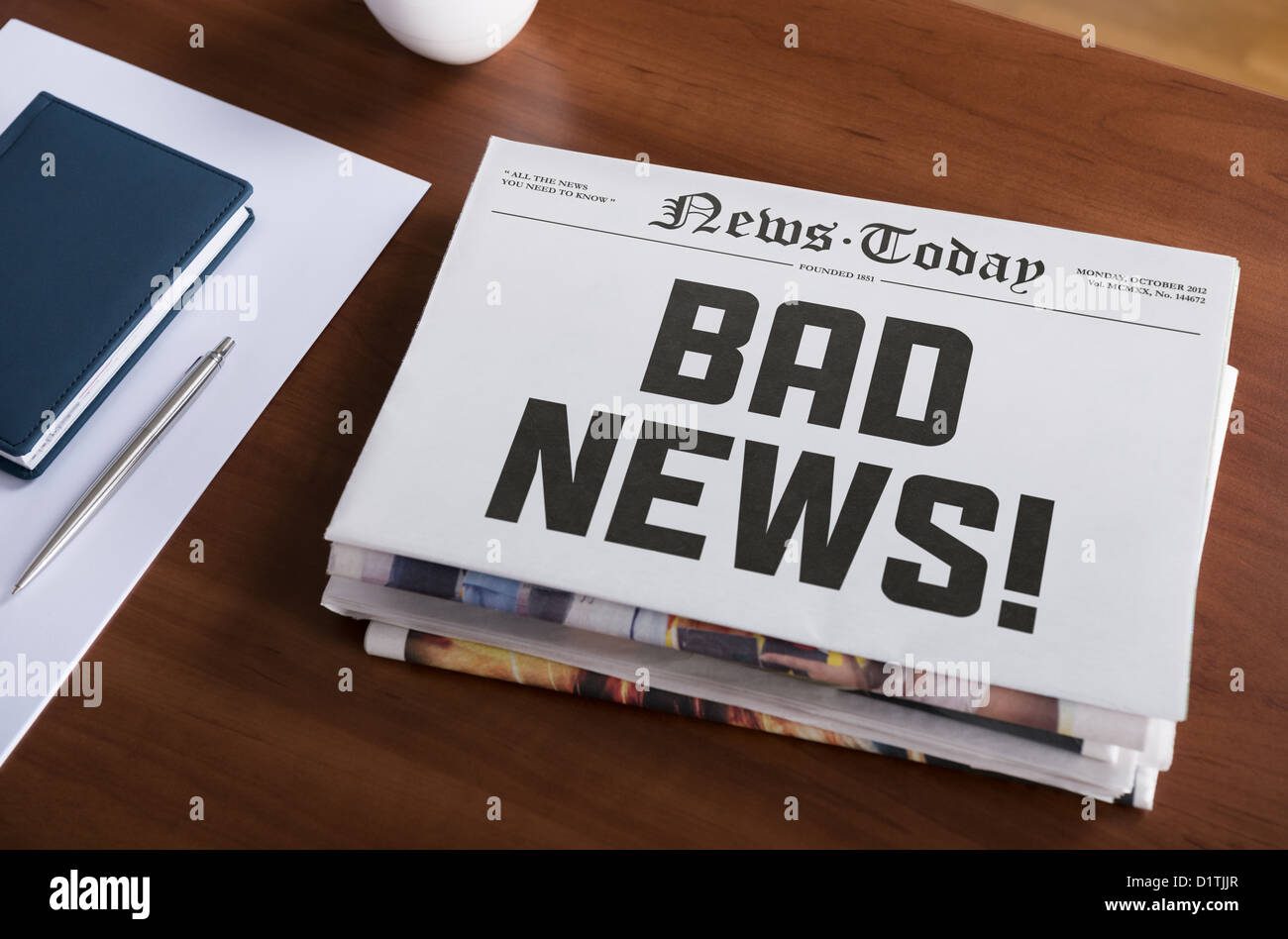Newspaper concept with hot topic 'Bad news' lying on office desk. - Stock Image