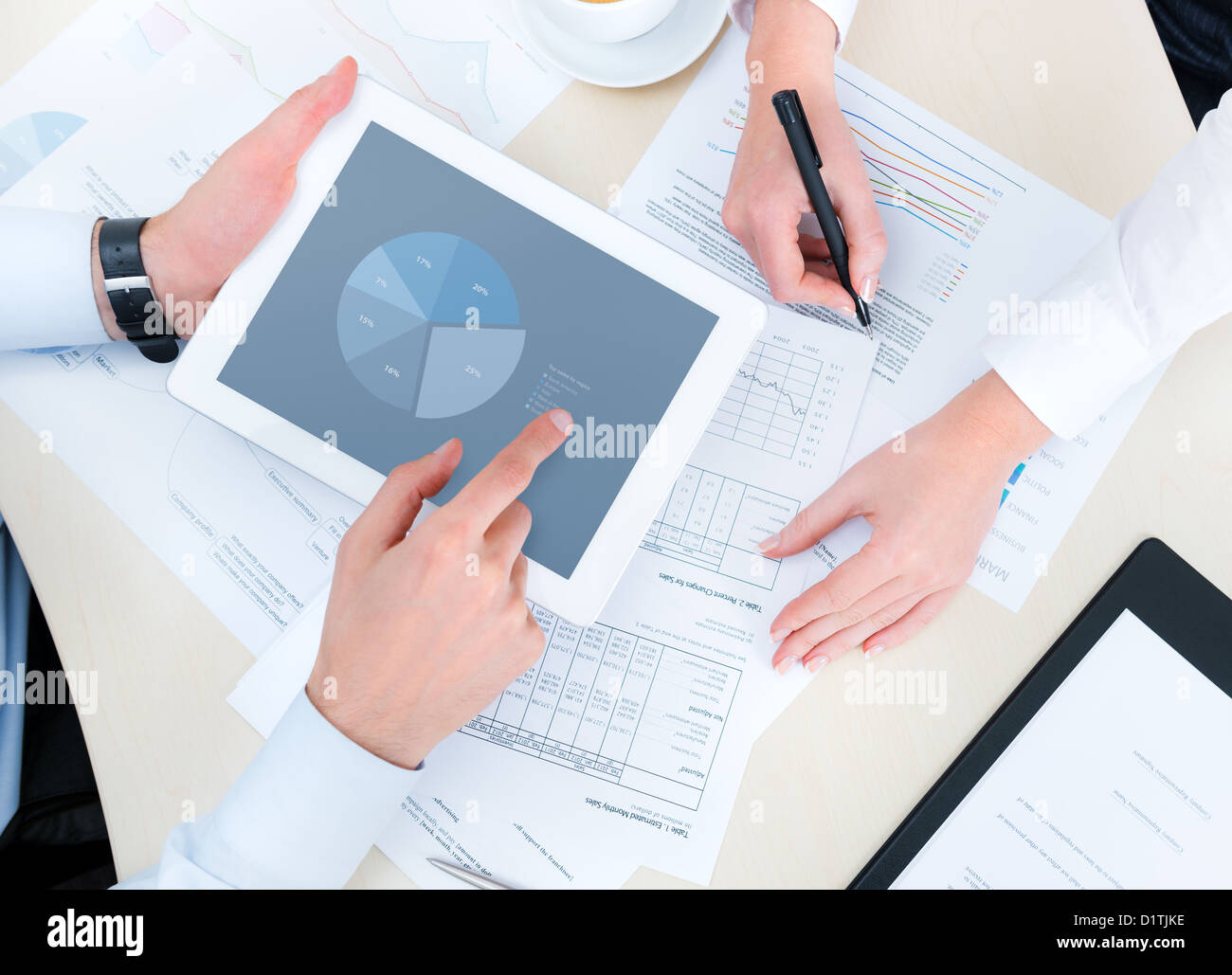 Business people developing a business project and analyzing market data information on a modern digital tablet computer. - Stock Image