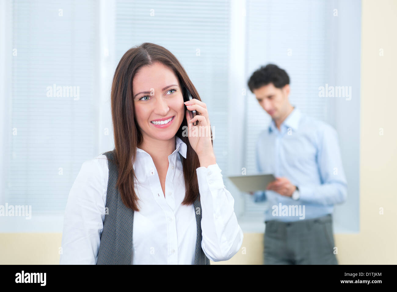 Beautiful young business woman speaks on a mobile phone. Young businessman with digital tablet on the background - Stock Image