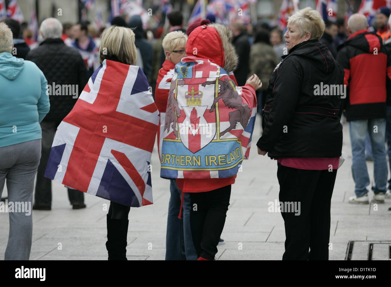 Belfast, UK. 5th Jan, 2013. Two women drape a Union jack and a Northern Ireland Flag across their back at the flag - Stock Image