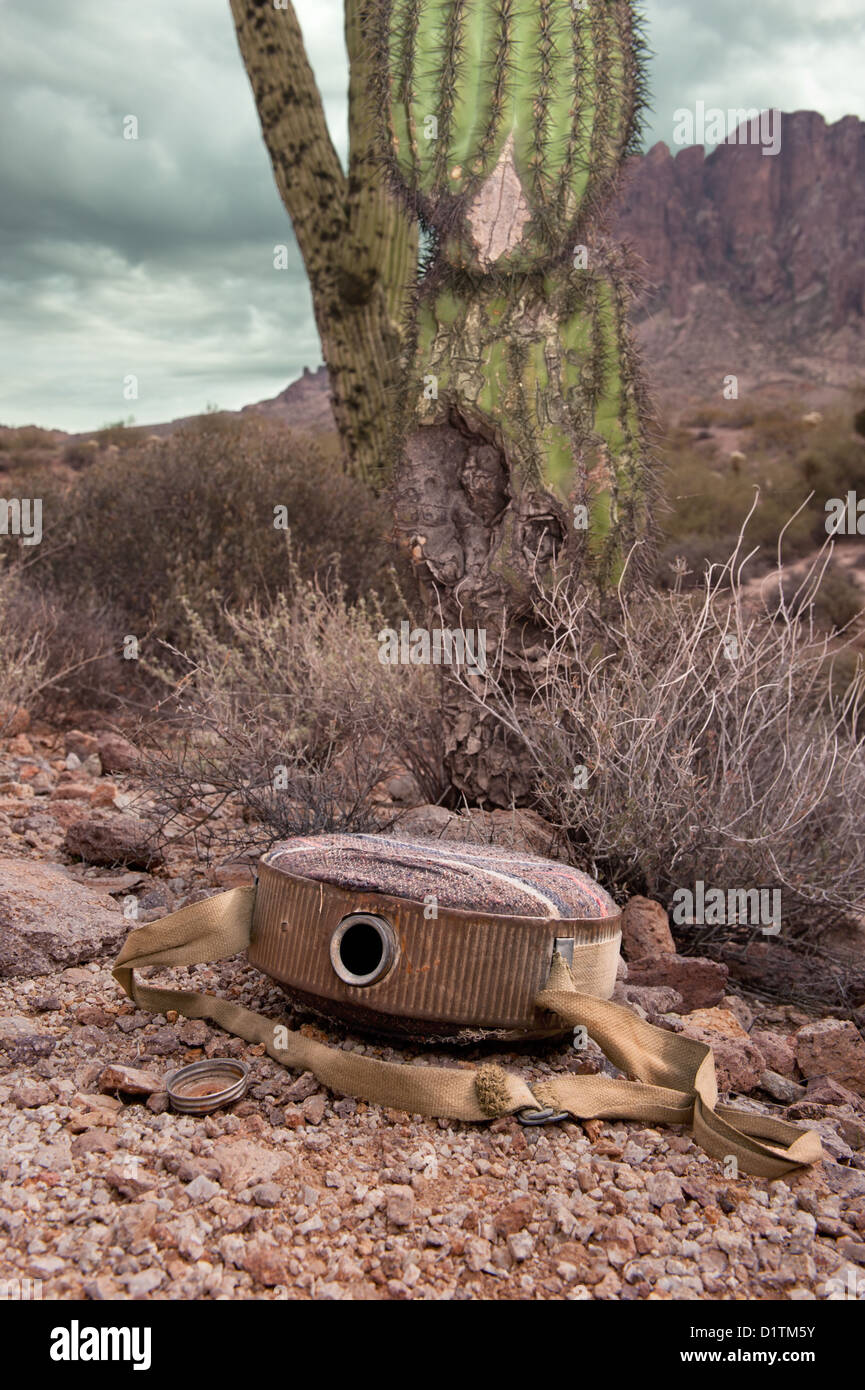 An old, vintage hiking canteen lies in a parched, dry desert, empty. - Stock Image