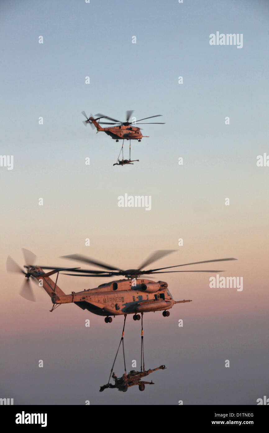 Two US Marine Corps CH-53E Super Stallion helicopters transport M777 towed 155 mm howitzers December 29, 2012 over - Stock Image